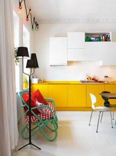 Проста біла фарба прекрасно контрастує з жовтою кухонними меблями